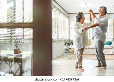 Romantic Asian Senior couple dancing at home. Happy Smiling Grandfather and Grandmother having fun Celebrating in wedding Anniversary day. Elderly man and woman holding hands together, Romance, lover