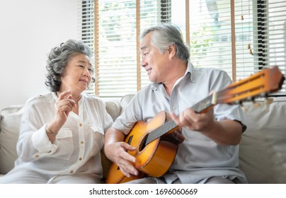 Romantic Asian senior Couple singing, playing acoustic guitar together. Happy Smiling Elderly Guitarist man and Old Vocalist woman having fun and enjoying their Retirement life. Lifestyle, Party