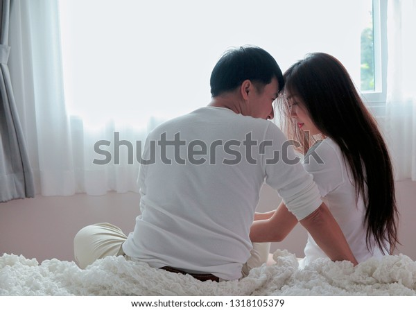 Romantic Asian young couple on bed in home or hotel, honeymoon sweet, vacation. The husband shows love to his wife, the idea of life that will revive sweetness.