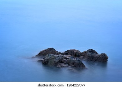 Romantic atmosphere in peaceful morning at sea. Big boulders sticking out from smooth wavy sea