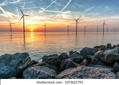 Romantic atmospheric sunset over the largest lake in the Netherlands (Ijsselmeer). Modern windmills stand in the water in a wind farm with a view from the dike.