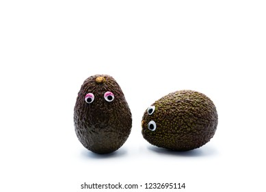 Romantic avocados couple with googly eyes as man and woman, funny food concept for creative projects.