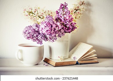 Romantic background with cup of tea ,lilac flowers and open book over white table
