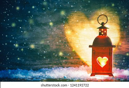 Romantic background or greeting card for Christmas or Valentines Day. Red lantern with a heart cut out lit by a glowing candle. Heart-shaped shadows on the wall