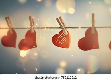 romantic background with hearts on clothes pegs and bokeh effect