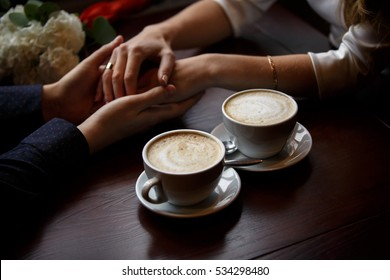 Romantic background, two cups of coffee and hands of couple in love on date. Romantic dinner in valentine's day