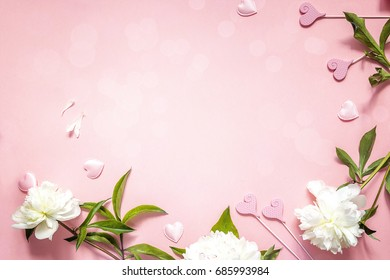 Romantic background with white peonies and decorative hearts on a pink.