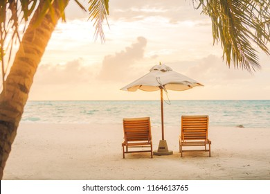 Romantic beach sunset for couple, honeymoon banner or background. Two beach lounge soft sunset light palm trees, beautiful sea view. Beach landscape, tropical scene