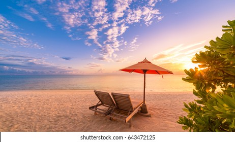 Romantic beach sunset with deck chairs and sun umbrella. Exotic tourism vacation banner design