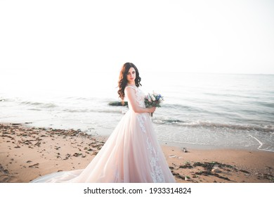 Romantic beautiful bride in white dress posing on the background sea