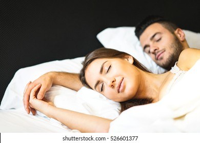 Romantic and beautiful couple sleeping peacefully on a bed with white sheets - Boyfriend and girlfriend sleeping together while holding hands
