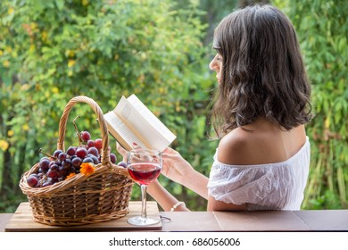Romantic and beautiful girl in morning light with vintage basket full of grape