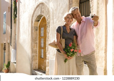 Romantic beautiful senior couple visiting old city street on vacation, taking selfies with photo camera, smiling outdoors. Healthy mature people traveling, leisure recreation technology lifestyle.