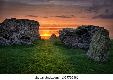 A romantic and beautiful view through the ruins of Aberystwyth Castle on the sunset on the horizon above the sea.