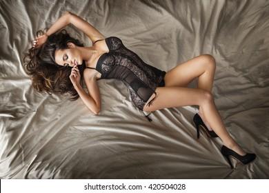 Romantic beautiful woman lying in bed, wearing sensual lingerie.