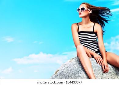 Romantic beautiful woman sunbathing on a seaside.