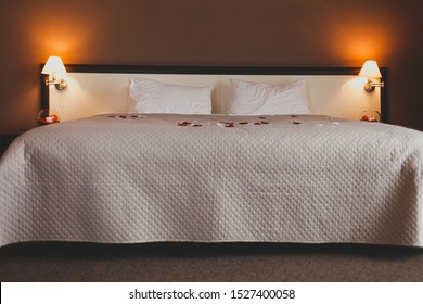 Romantic bed in a beautiful hotel room. Large bed with rose petals for a romantic evening