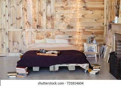 Romantic bedroom in warm colors with a lot of garland lights Reading of lovely book with a cup of cacao or tea. Beautiful evening for a couple under garland lights . Christmas mood