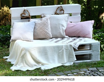 Romantic bench full of cushions in shadowy garden for lovers. Bench made from wood pallets  painted with white color.
