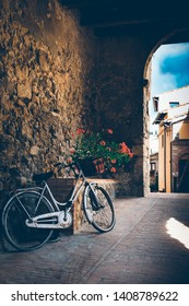 Romantic Bicycle decorated with flowers in basket on front of ancient wall