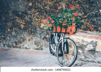 Romantic Bicycle decorated with flowers in basket in front of ancient wall