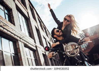 Romantic biker couple with black motorcycle. Handsome bearded man and young attractive woman outdoors with cafe racer.