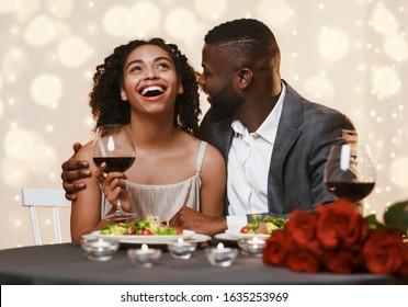Romantic black man courting his pretty girlfriend while having valentine dinner in restaurant