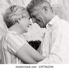 Romantic black and white portrait of senior tourist couple hugging on holiday with heads together, smiling outdoors. Mature mand and woman enjoying leisure travel lifestyle, retirement activities.
