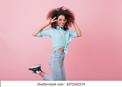 Romantic black-haired woman in vintage outfit jumping in front of pink wall and touching curly hair. Pretty lovable black girl enjoying photoshoot in studio in weekend.