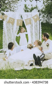 romantic boho wedding outside in green, bride and make Groom along with their two sweet flower children a romantic picnic under the love banner