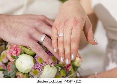 romantic boho wedding outside in green, bride and groom showing their wedding rings on the fingers, detail