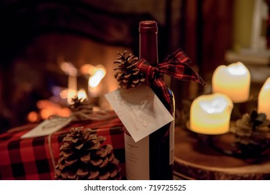 romantic bottle of wine and Christmas gift on table by fireplace on Christmas