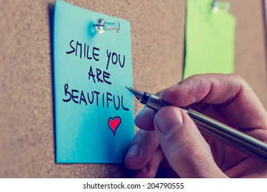 Romantic boyfriend writing Smile you are beautiful message on a blue post it paper with a vintage style filter effect.