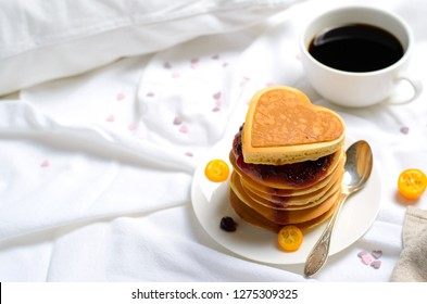 Romantic Breakfast in Bed, Pancakes and Coffee on White Bed Sheet, Top View