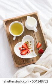 romantic breakfast in bed.  Yogurt with granola and strawberry in  bowl in  shape of heart and cup of  tea, top view.