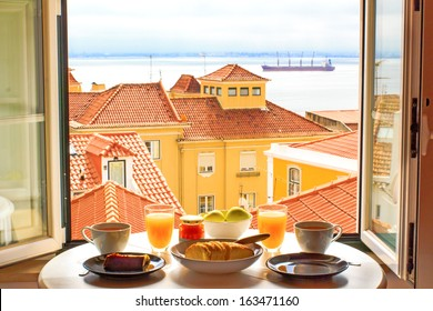 Romantic breakfast by window with a view in Lisbon, Portugal