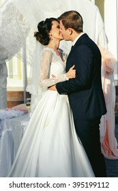 Romantic bride & groom kissing at wedding aisle during ceremony