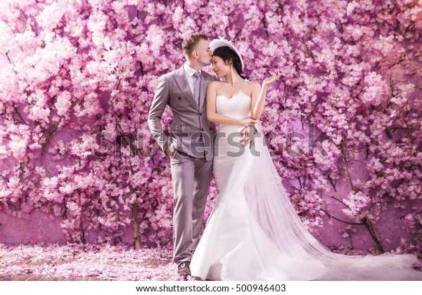 Romantic bridegroom kissing bride on forehead while standing against wall covered with pink flowers