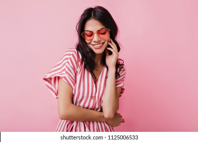 Romantic brown-haired girl in trendy heart glasses posing with shy smile. Indoor photo of graceful young woman in summer attire and accessories.