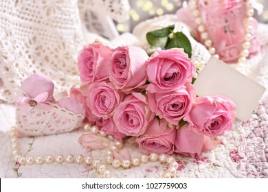 romantic bunch of pink roses with blank greeting card lying on the bed
