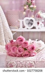 romantic bunch of pink roses lying on the bed in shabby chic style interior