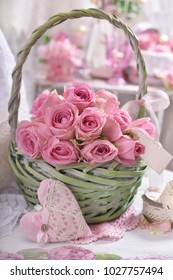 romantic bunch of pink roses with paper tag in green wicker basket in shabby chic style interior