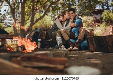 Romantic camping couple sitting by bonfire in open air. Loving man and woman relaxing near campfire.
