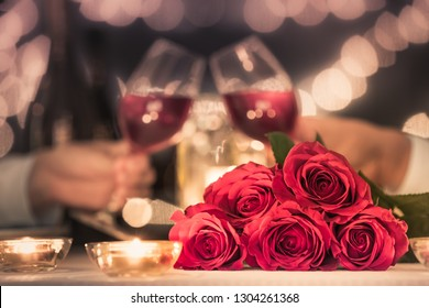Romantic candle light dinner. Couple enjoying wine at dinner table next to bouquet of red roses.