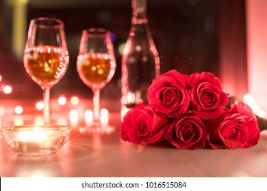 Romantic candle light and red roses setting.