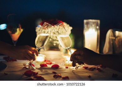Romantic candlelight dinner for couple table setup at night. Man & Woman hold glass of Champaign. Concept for valentine's day or date. - Shutterstock ID 1010722126