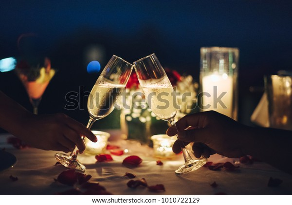 Romantic candlelight dinner for couple table setup at night. Man & Woman hold glass of Champaign. Concept for valentine's day or date.