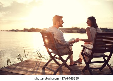 romantic caucasian couple sitting on chairs by the river holding hands, talking, watching each other. copy space