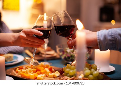 Romantic celebrating relationship toasting with red wine. Happy cheerful young couple dining together in the cozy kitchen, enjoying the meal, celebrating anniversary romantic toast.