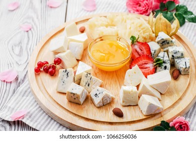 Romantic cheese plate Assortment of various types of cheese on wooden cutting board with pink flowers. Close up. seria of photo